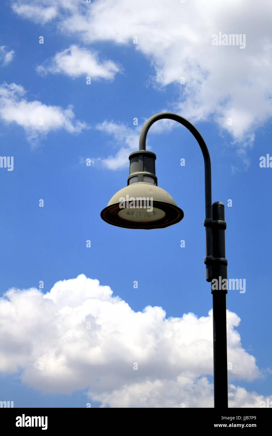 A shepherd hook street lamp with trumpet hood stands against blue sky with billowing white clouds. - Stock Image