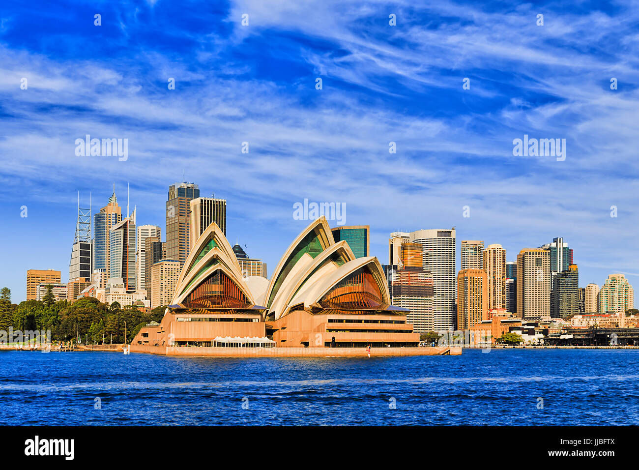 Modern cityline of Sydney city CBD landmarks as seen from passenger ferry in mid harbour on a sunny bright day under - Stock Image