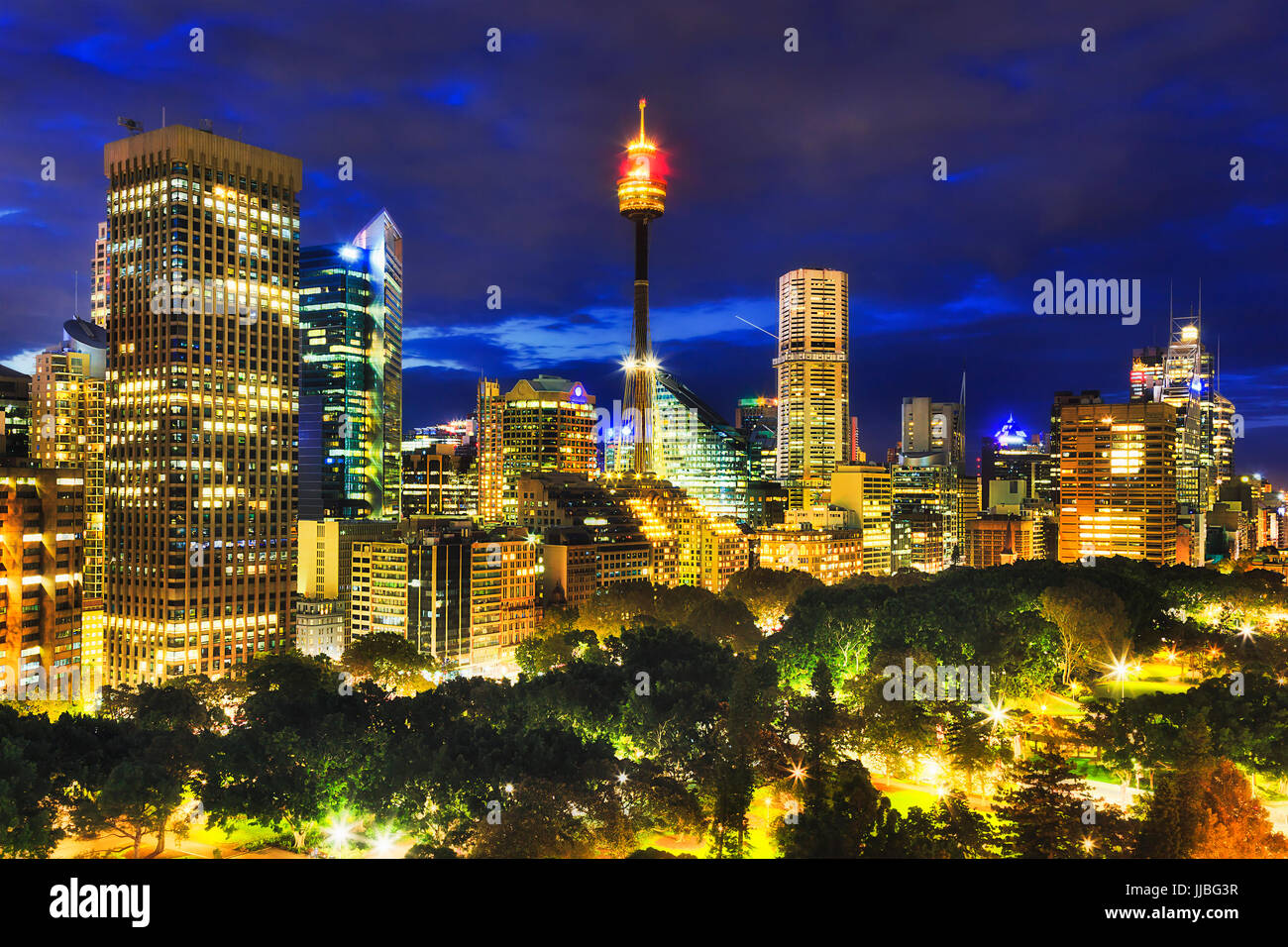 Panorama of Sydney city high-rise towers illuminated at sunset standing over green trees of the central Hyde Park. - Stock Image