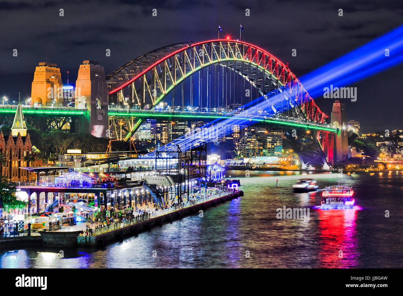 Sydney harbour bridge brightly illuminated and sending blue beams of projector light during Vivid Sydney light and ideas show in Sydney CBD as seen fr Stock Photo