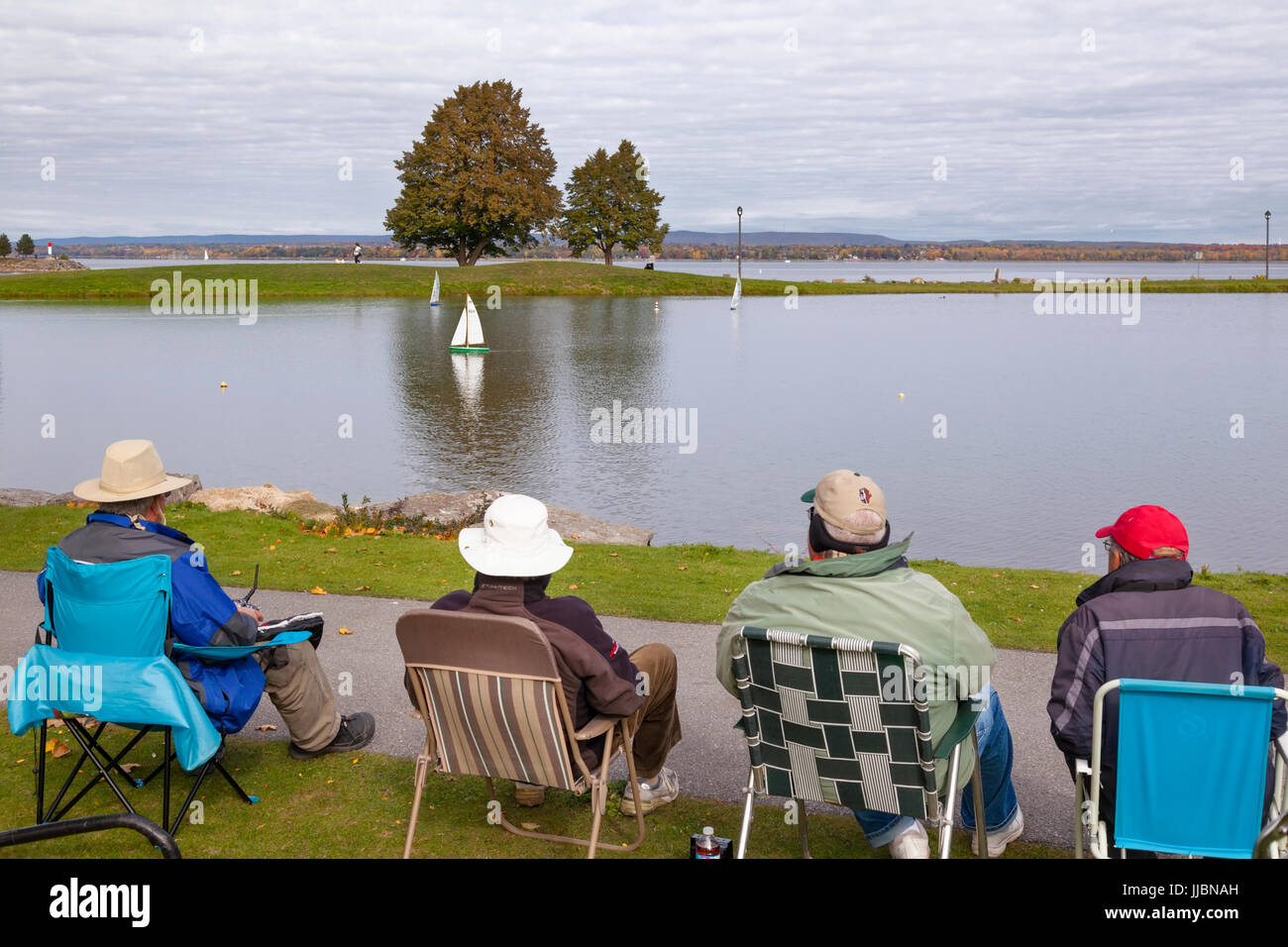 People sitting in chairs using radio controlled boats on a small pond  at Andrew Haydon Park in Ottawa, Ontario, - Stock Image