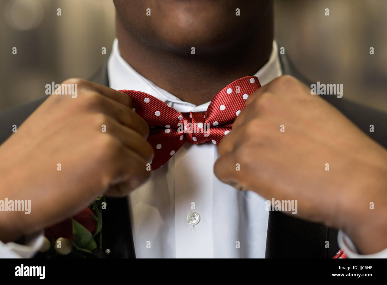 c4dcb26683b3 One teen boy adjusts polka dotted red bow tie. Getting dressed and ready  for formal high school prom dance.