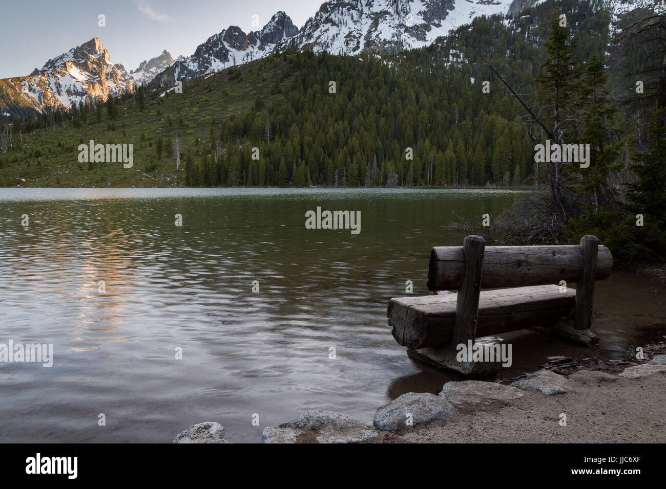 String Lake experiencing a large snow runoff causing the lake to flood areas around a bench. Grand Teton National Stock Photo