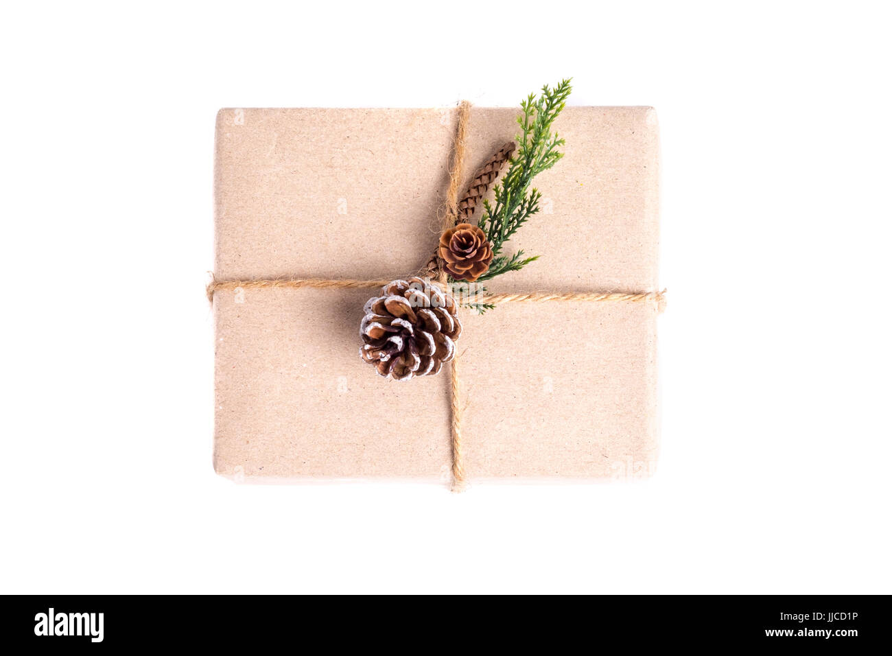 Brown paper craft warped on present box decorate with pine cone and green leaf isolated on white background,Gift - Stock Image