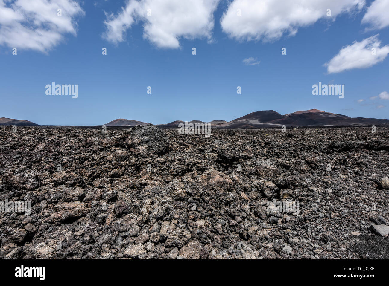 Black lava field in the bizarre volcanic landscape of Timanfaya National Park on a sunny day. Lanzarote, Canary - Stock Image