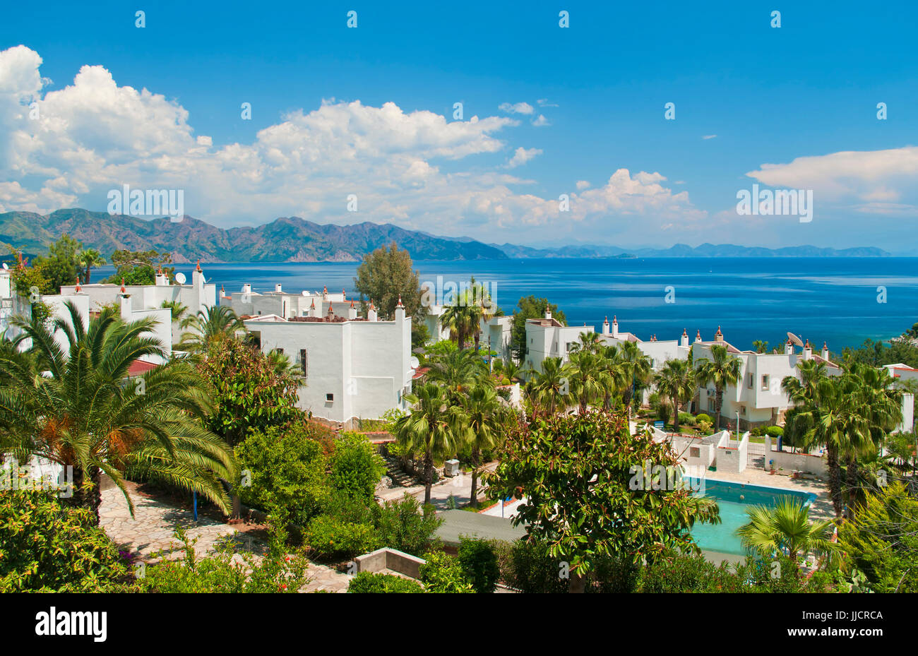 white villas with palm trees in Profesorler Sitesi at Amos Bay in Aegean sea with mountainous islands and clouds Stock Photo