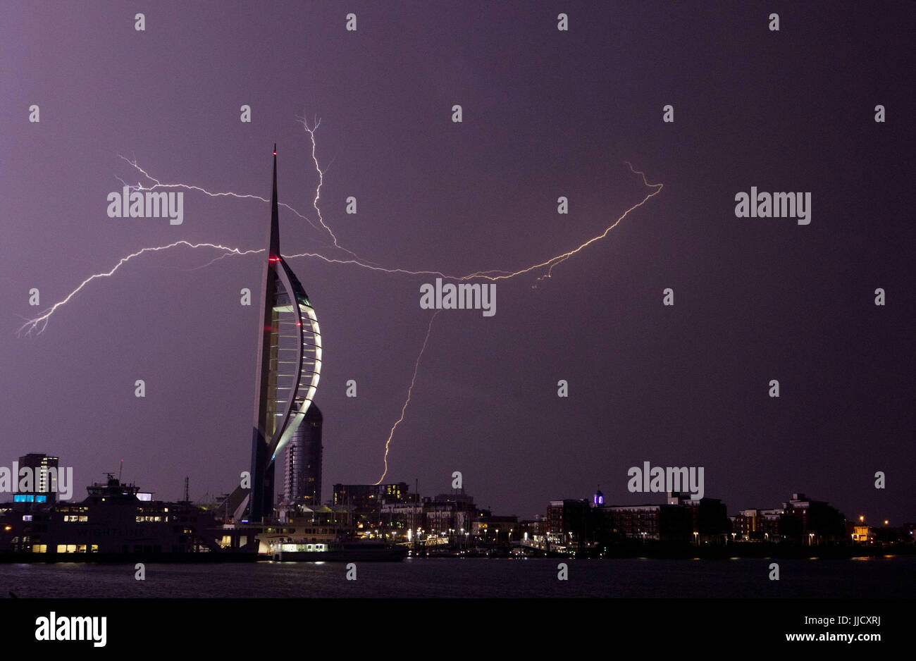 Lightning flashes near the Spinnaker Tower in Portsmouth as overnight thunderstorms swept across Britain. Stock Photo