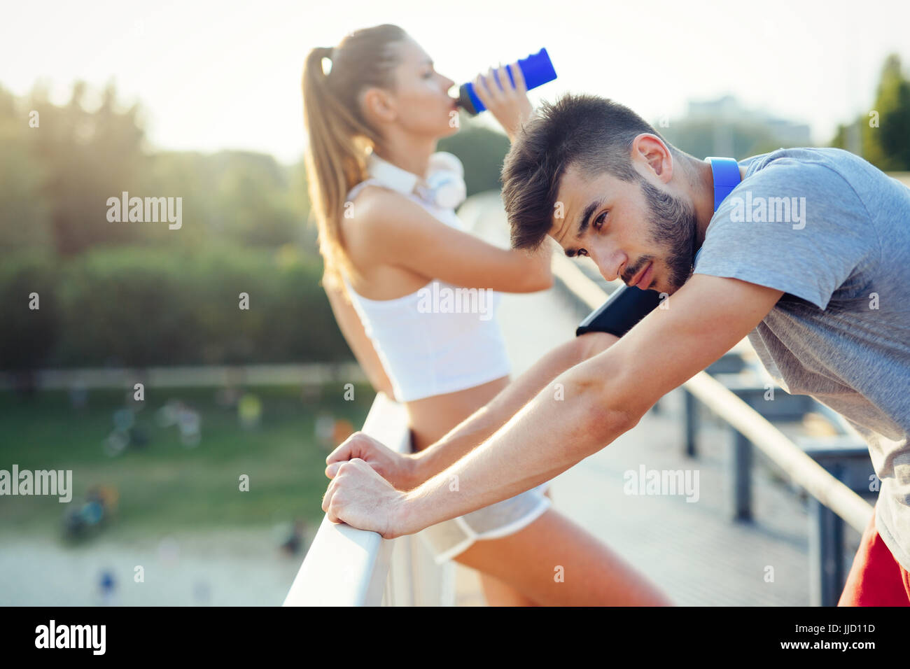 Portrait of man and woman during break of jogging - Stock Image
