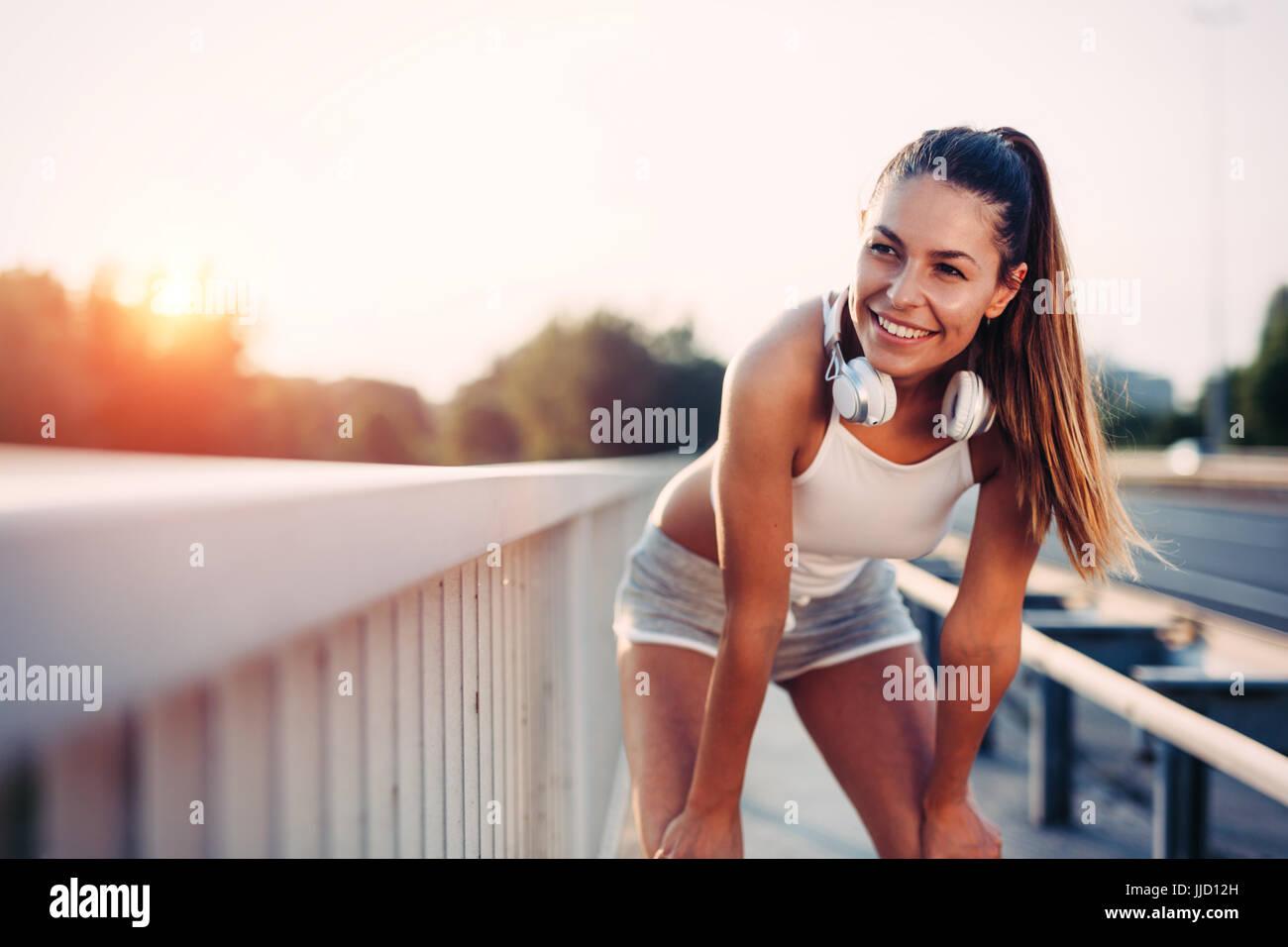 Portrait of woman taking break from jogging - Stock Image