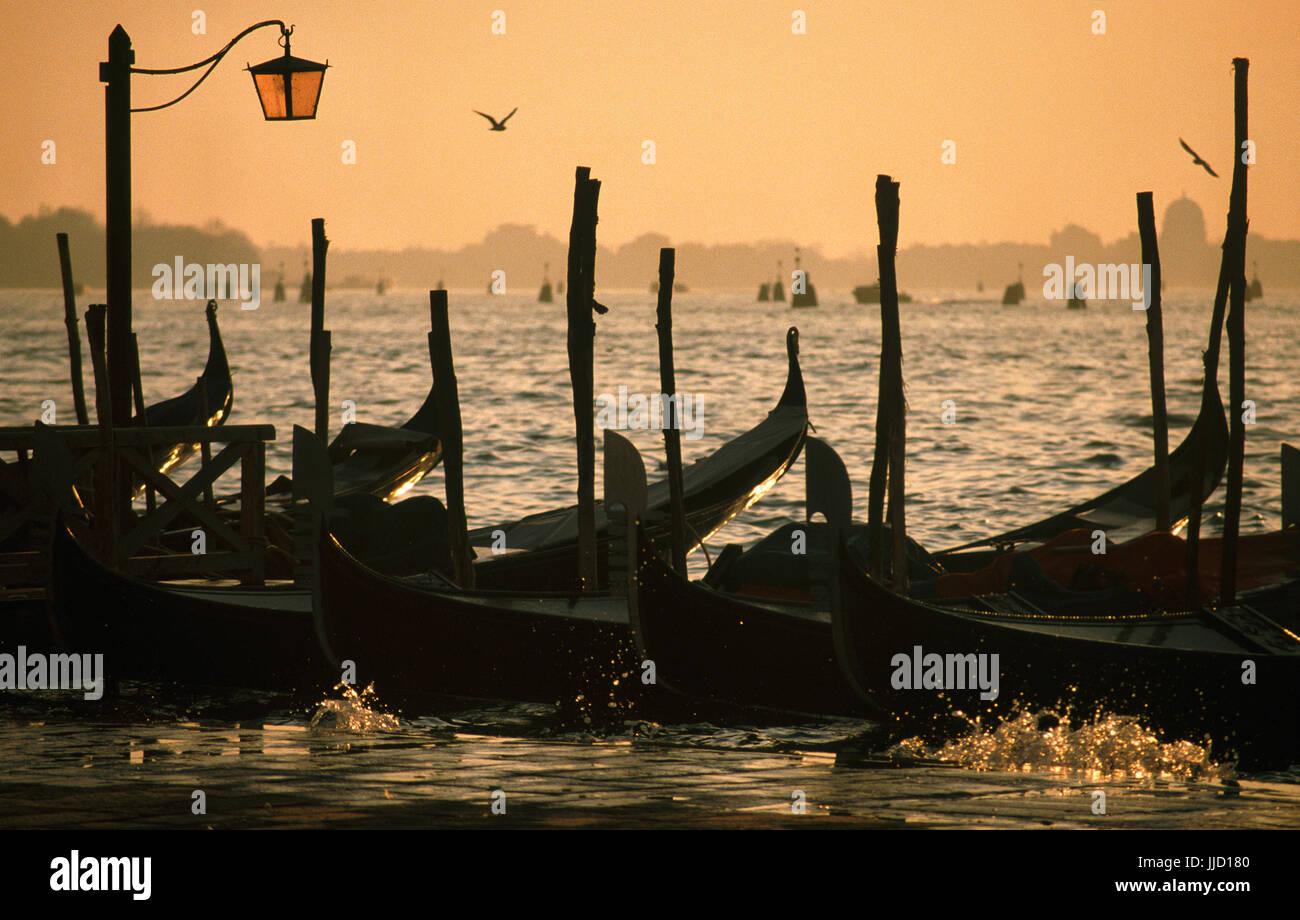 Venedig:Gondeln am Kai,Wasser-Spritzer, Morgensonne, * gVenice early morning: gondole fixed at edge of Piazza San - Stock Image