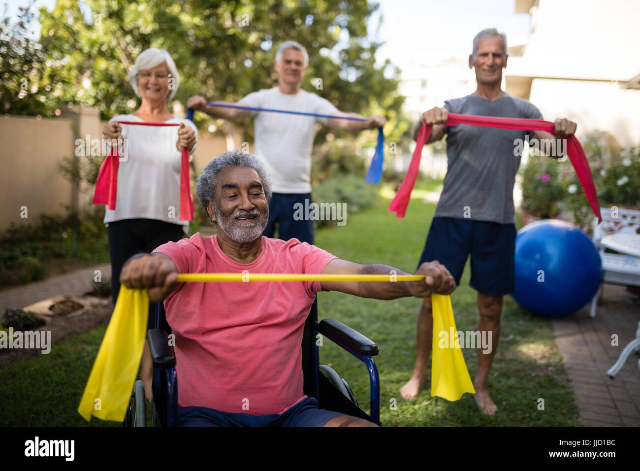 Physically impaired senior man holding ribbon with friends while exercising at park - Stock Image