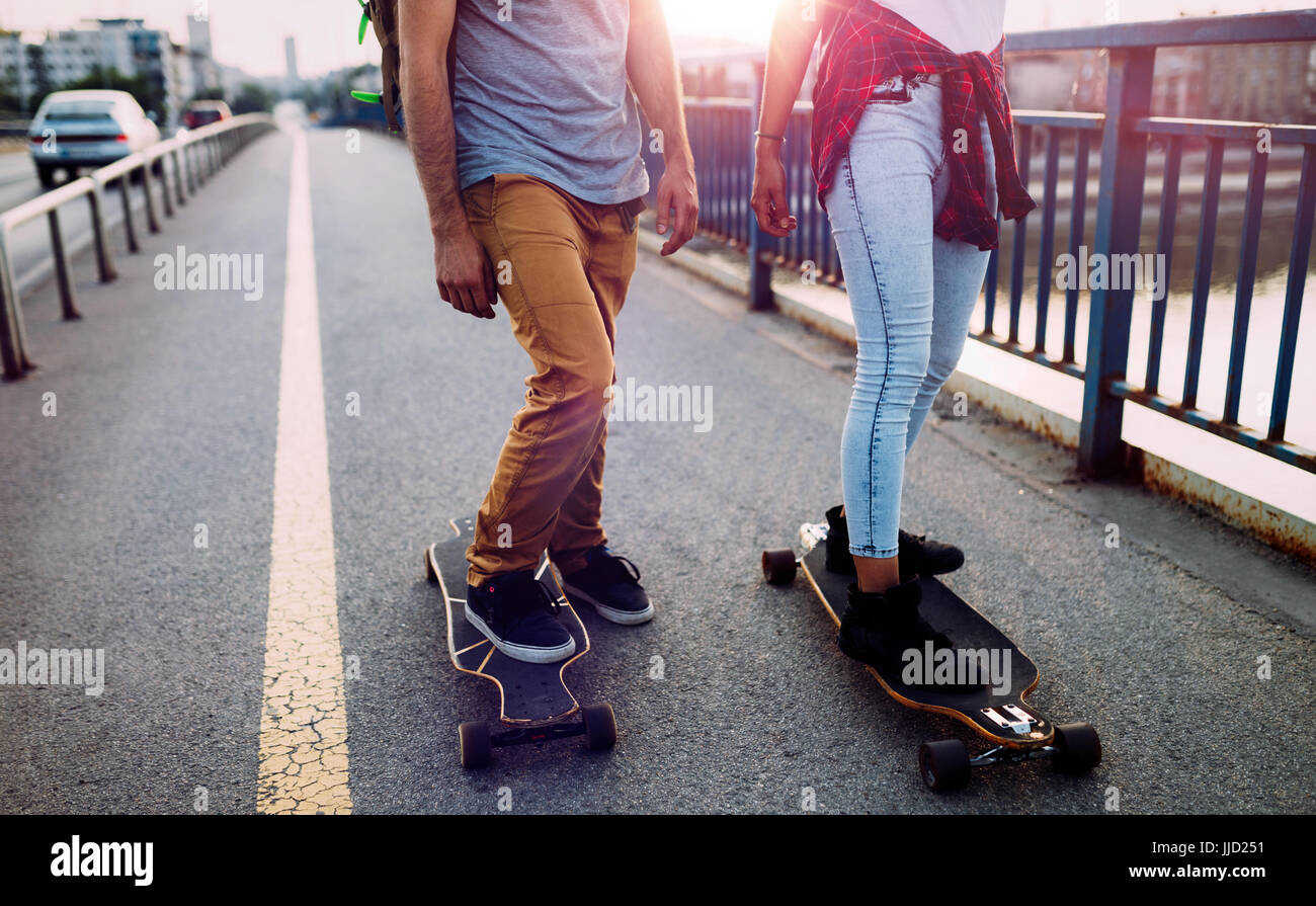 Young attractive couple riding skateboards and having fun - Stock Image