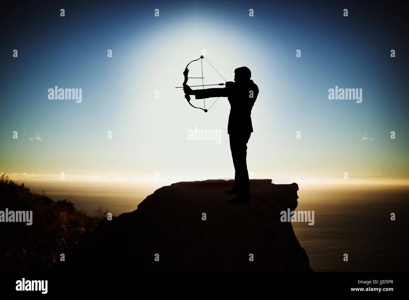 Silhouette businessman taking aim with bow and arrow  against scenic view of mountain by sea against sky - Stock Image