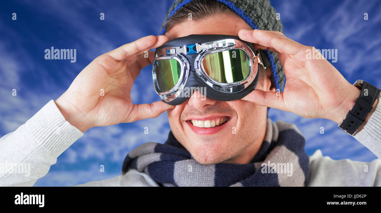 Happy man wearing aviator goggles against view of the blue sky Stock Photo