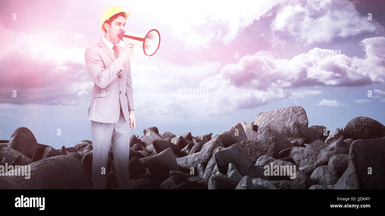 Young architect yelling with a megaphone against blue sky - Stock Image