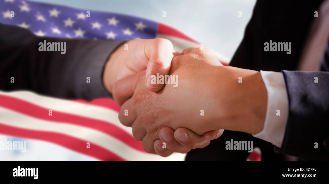 Male and female corporates shaking hands against composite image of low angle view of american flag - Stock Image