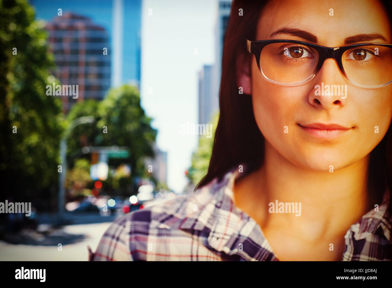 Close up portrait of young woman wearing eyeglasses  against blur view of a modern city Stock Photo