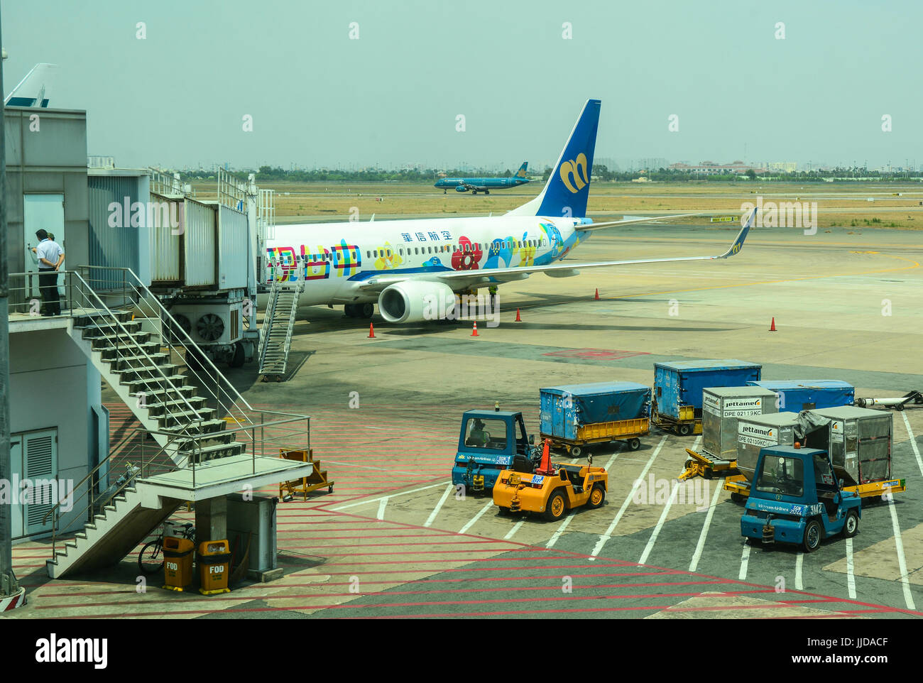 Saigon, Vietnam - Mar 9, 2016. Civil aircraft docking at Tan Son Nhat Intl Airport in Saigon, Vietnam. The airport - Stock Image