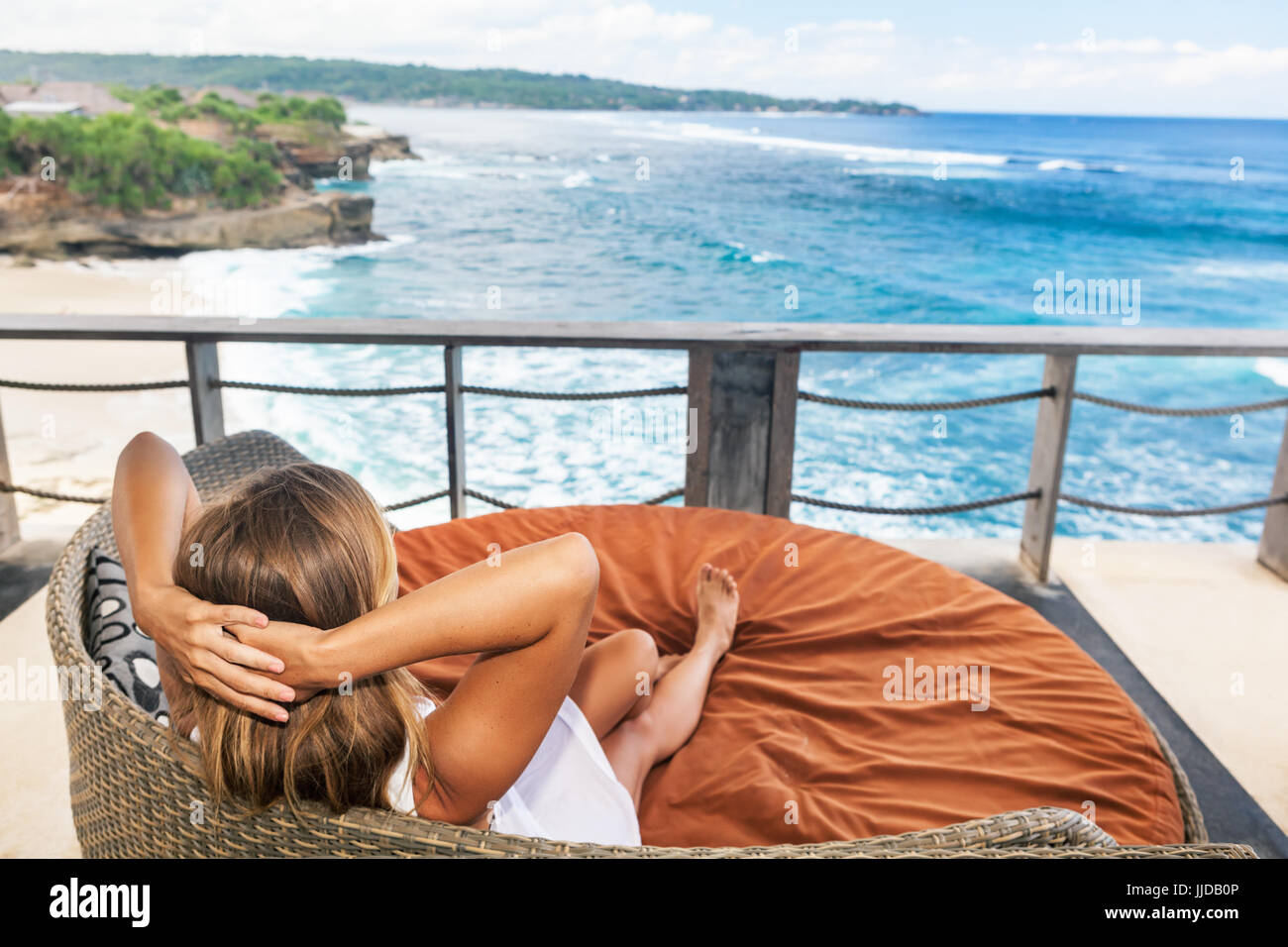 Young happy woman relaxing in lounge on roof veranda with beautiful tropical sea view. Positive girl look at ocean - Stock Image
