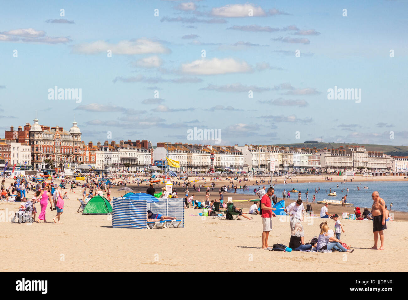 2 July 2017: Weymouth, Dorset, England, UK - People sunbathing on the busy beach on a hot summer day. - Stock Image
