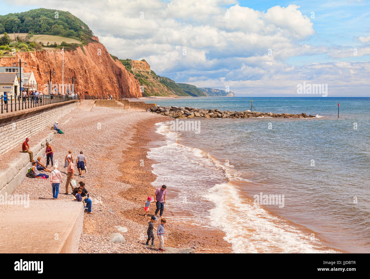 3 July 2017: Sidmouth, Dorset, England, UK - Visitors on the shingle beach on a bright summer day. - Stock Image