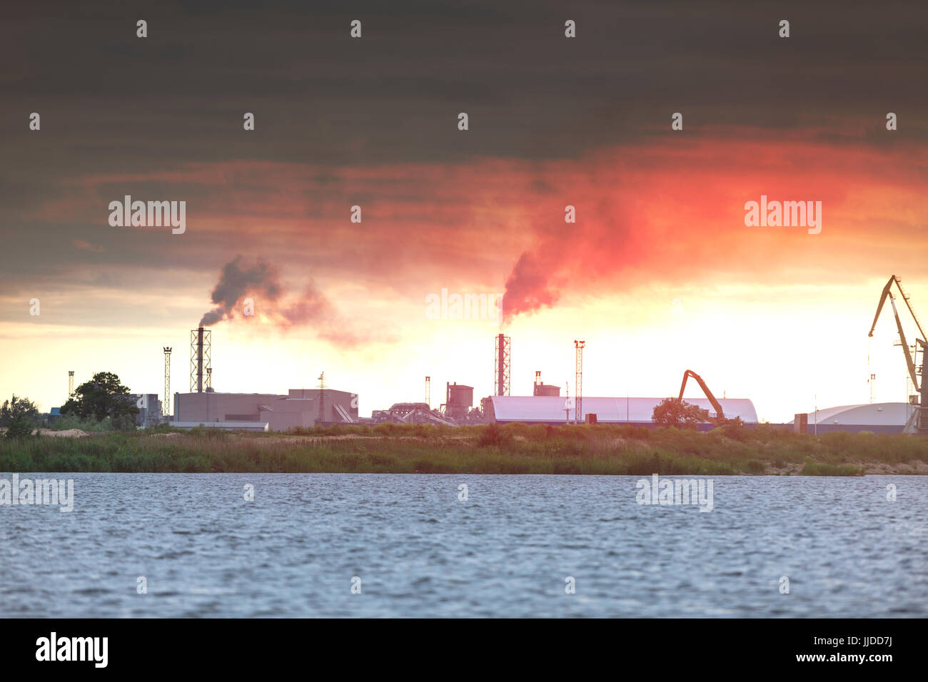 Air pollution by smoke coming out of two factory chimneys. Industrial zone in the city - Stock Image