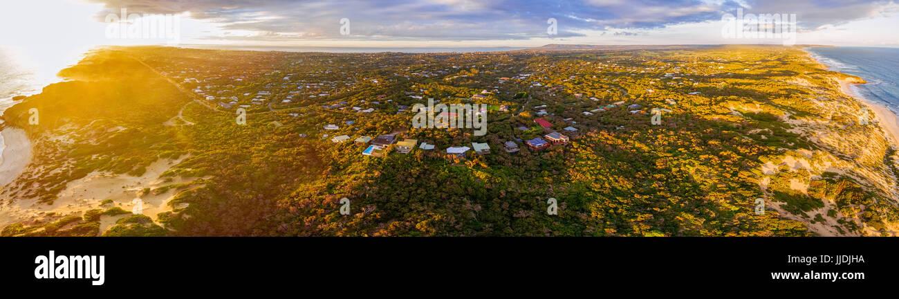 Aerial panorama of luxurious vacation homes in lush coastal vegetation at sunset. Morningon Peninsula, Melbourne, - Stock Image