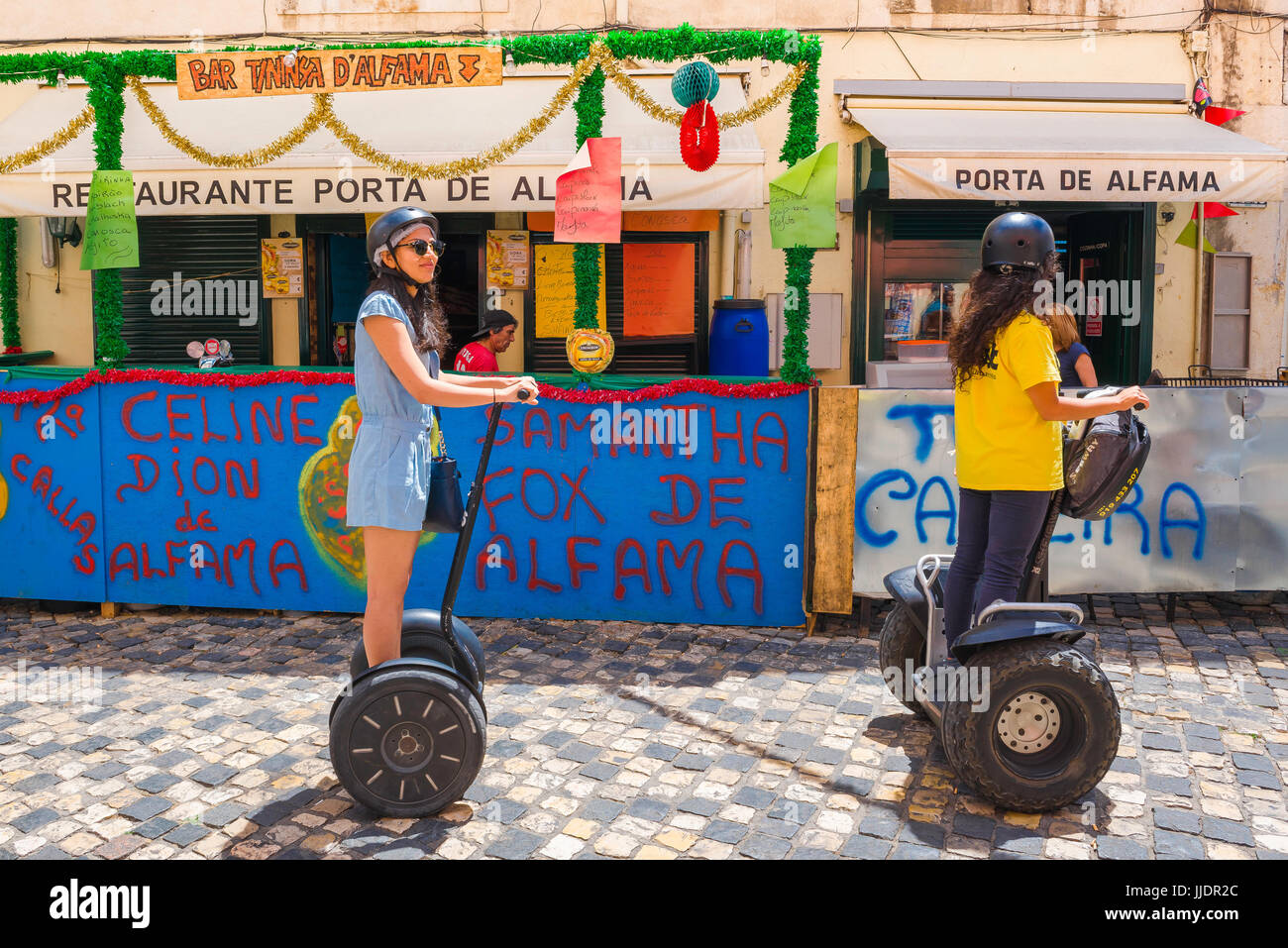 Lisbon Alfama tourists, two young women tour the old town Alfama district of Lisbon on segways, Portugal. - Stock Image