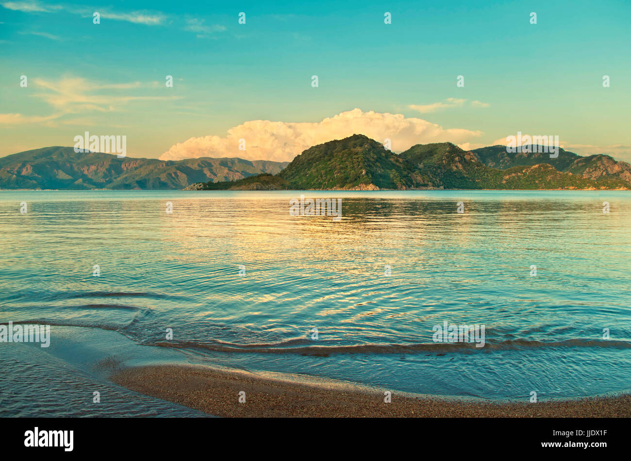 cross-processed green and yellow image of Icmeler beach on Aegean sea cost during sunset, Marmaris, Turkey - Stock Image