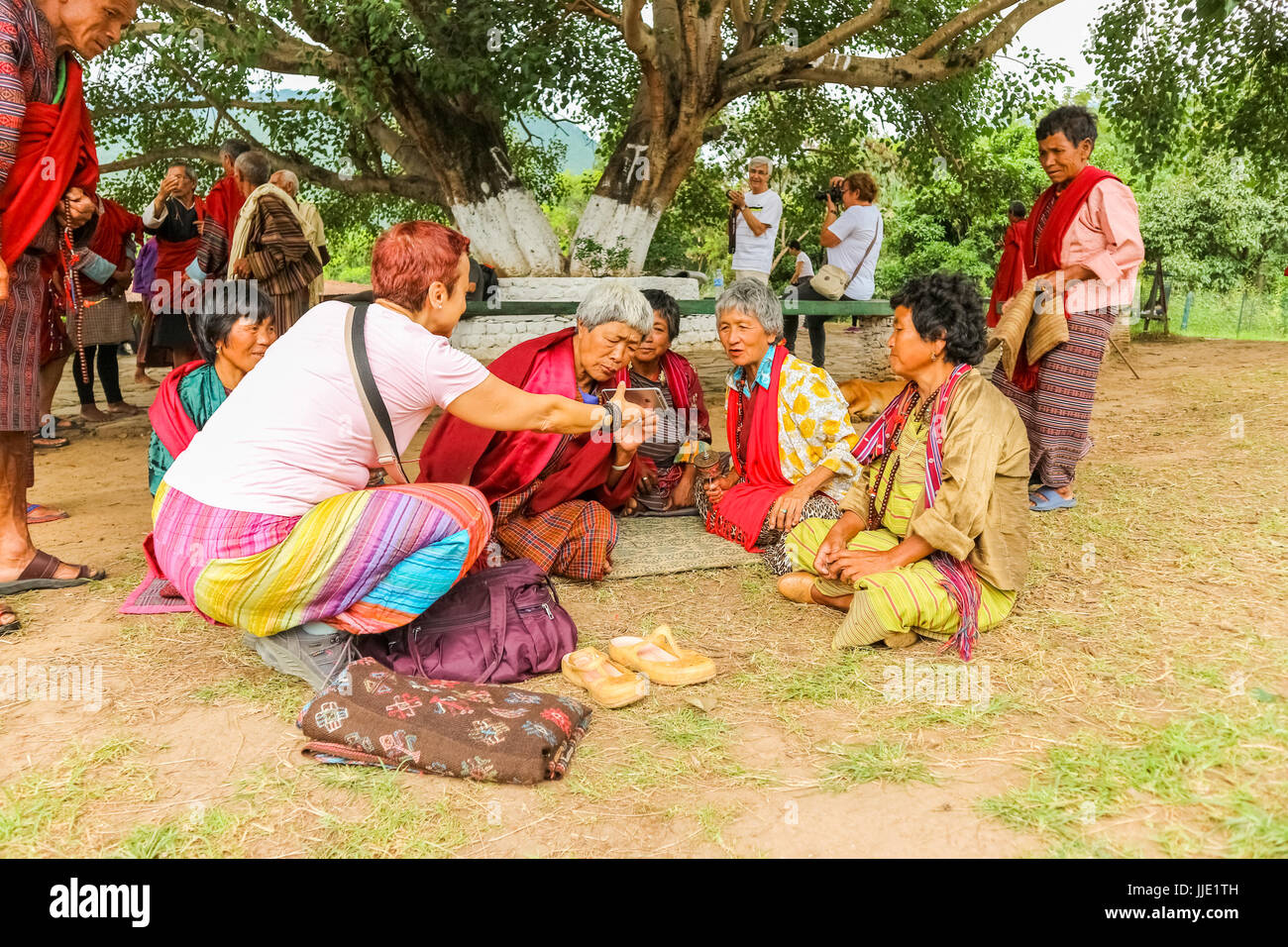 Thimphu, Bhutan - September 15, 2016: Caucasian woman showing pictures on her mobile to Bhutanese people in traditional - Stock Image