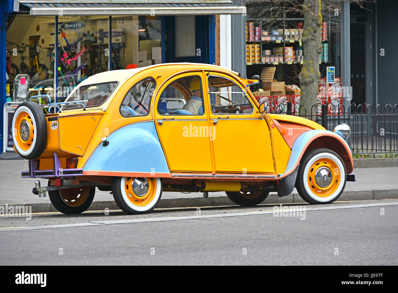 Citroen 2cv French car well maintained in unusual colours with rear mounted extended boot box & tow bar seen on Stock Photo