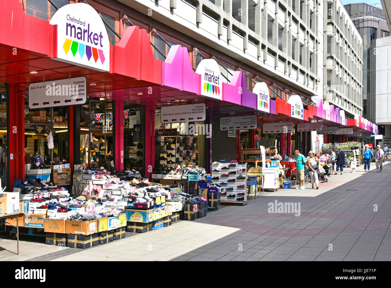 Chelmsford Essex town centre covered market with goods on display along pedestrianised pavement below multi storey - Stock Image