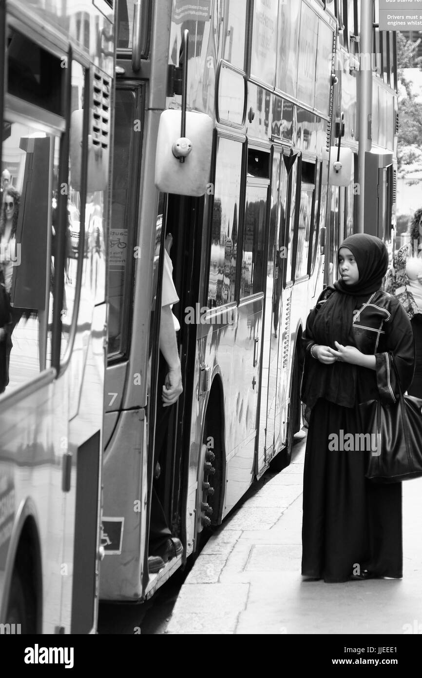 A young Muslim woman appears to have trouble gettng on a London bus - Stock Image