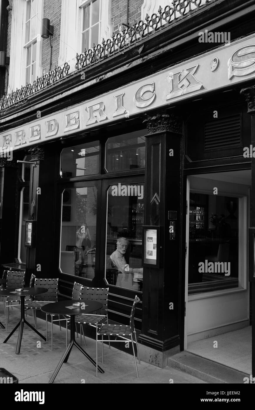 Man sitting alone looking sadly out of the window of Frederick's bar and restaurant in Camden Passage, Islington, - Stock Image