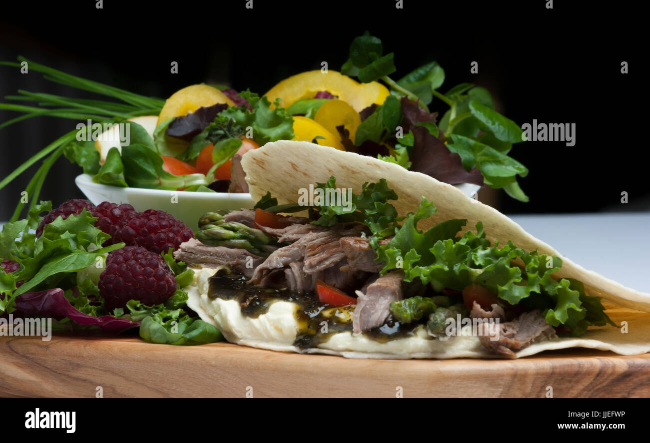 Pulled Spicy Lamb wrap with fresh salad and summer fruits on a wooden chopping board - Stock Image
