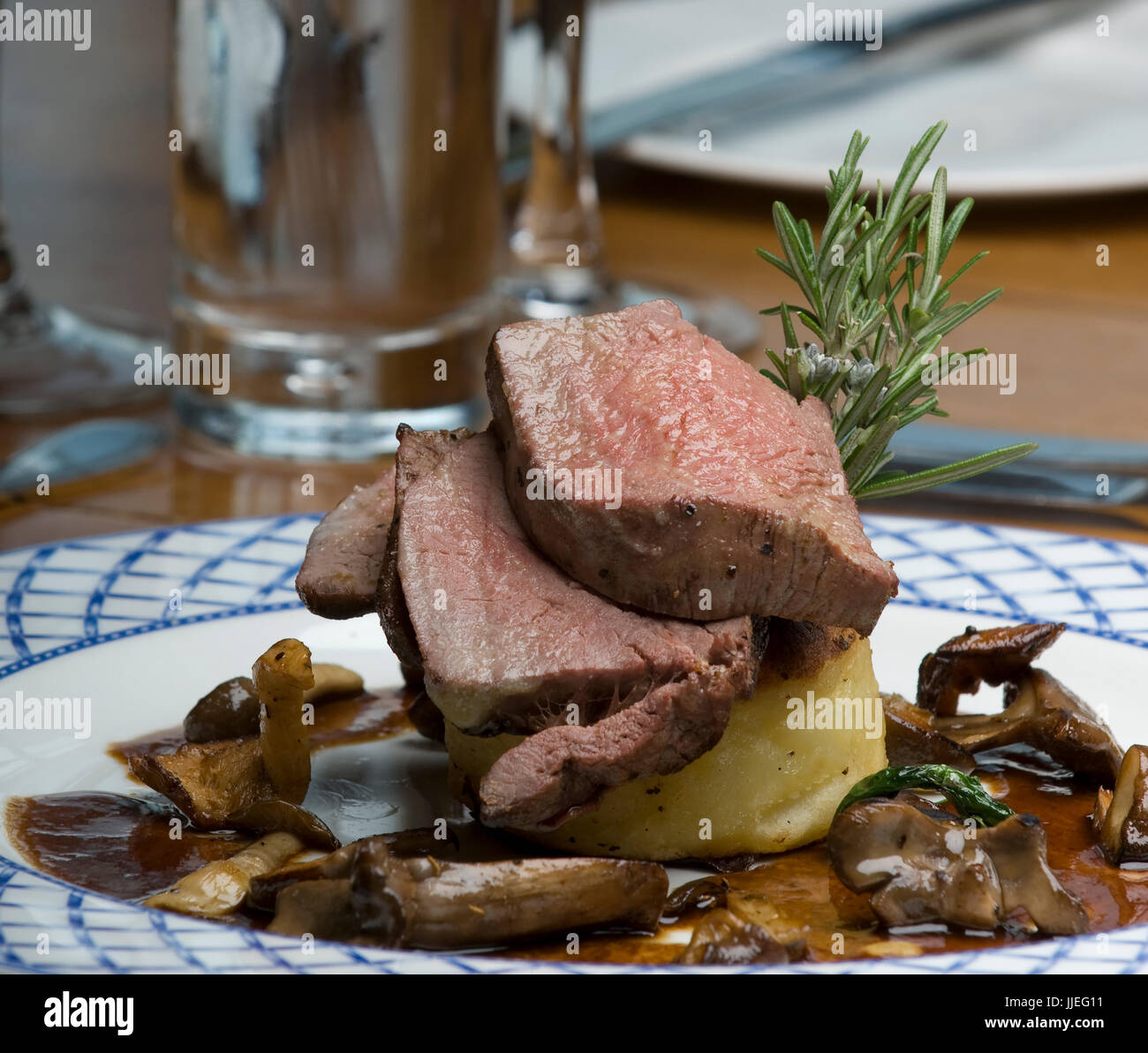 A Plate of Succulent Roast Lamb with Sauteed chanterelle mushrooms with a rosemary gravy - Stock Image