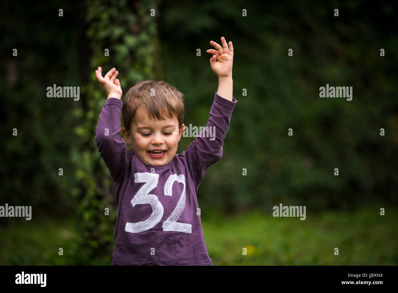 a69059e2c5d48 Happy cute little boy at park with raised hands Stock Photo ...
