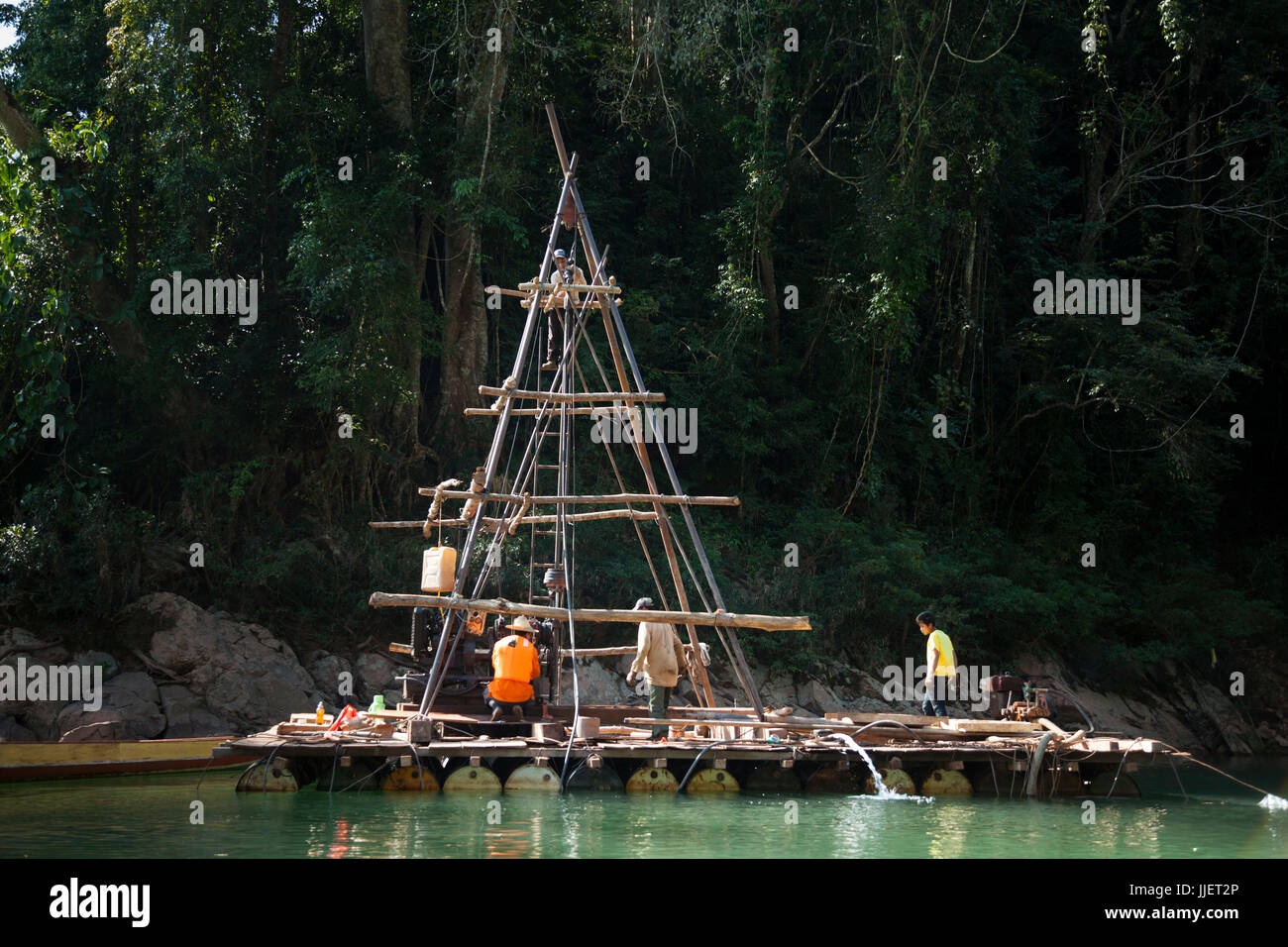 A drill rig collects core samples in a natural constriction of the Nam Ou River where Dam #7 is planned for construction, - Stock Image