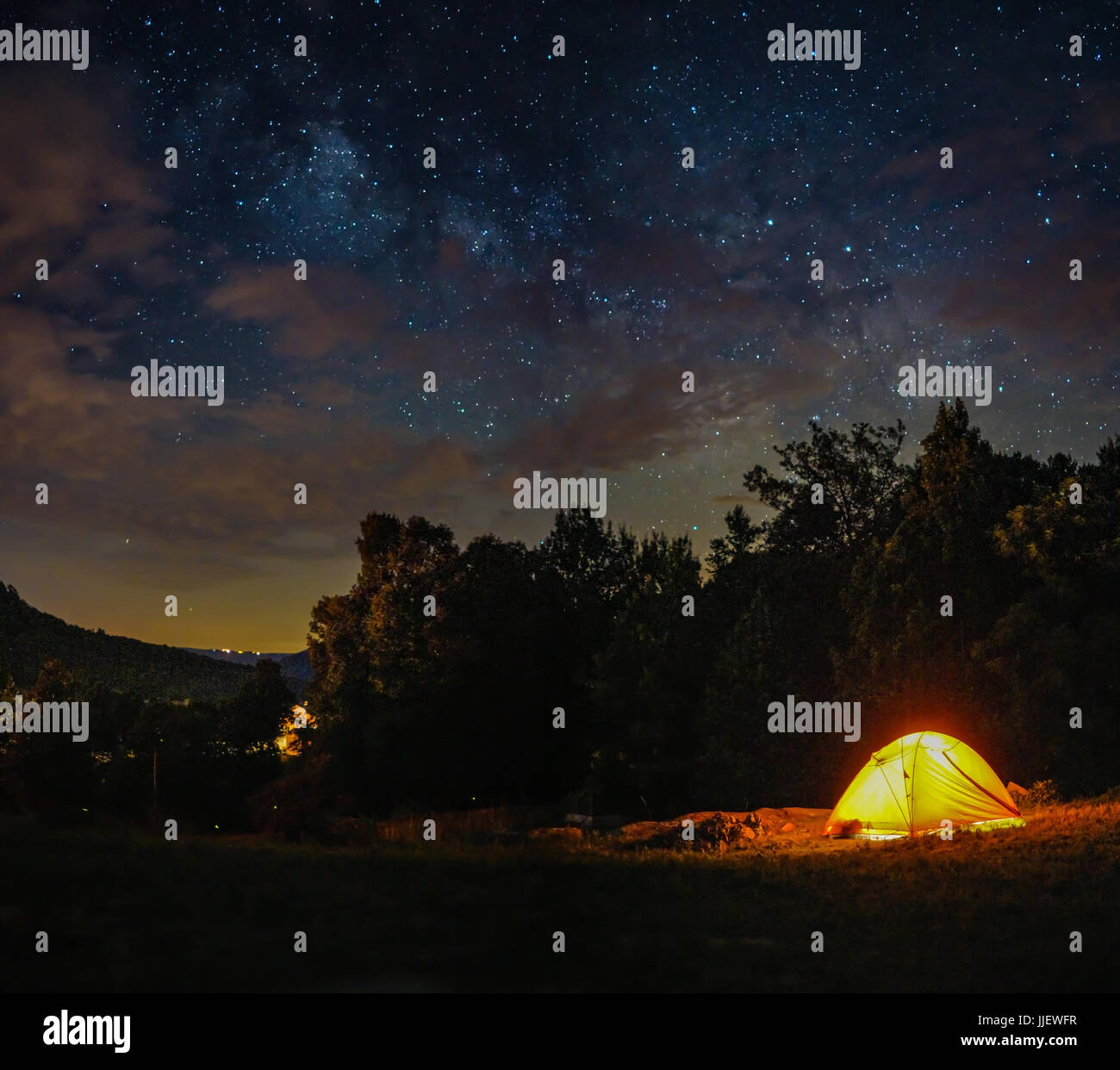 A camping tent under milky way sky and twilight at night - Stock Image
