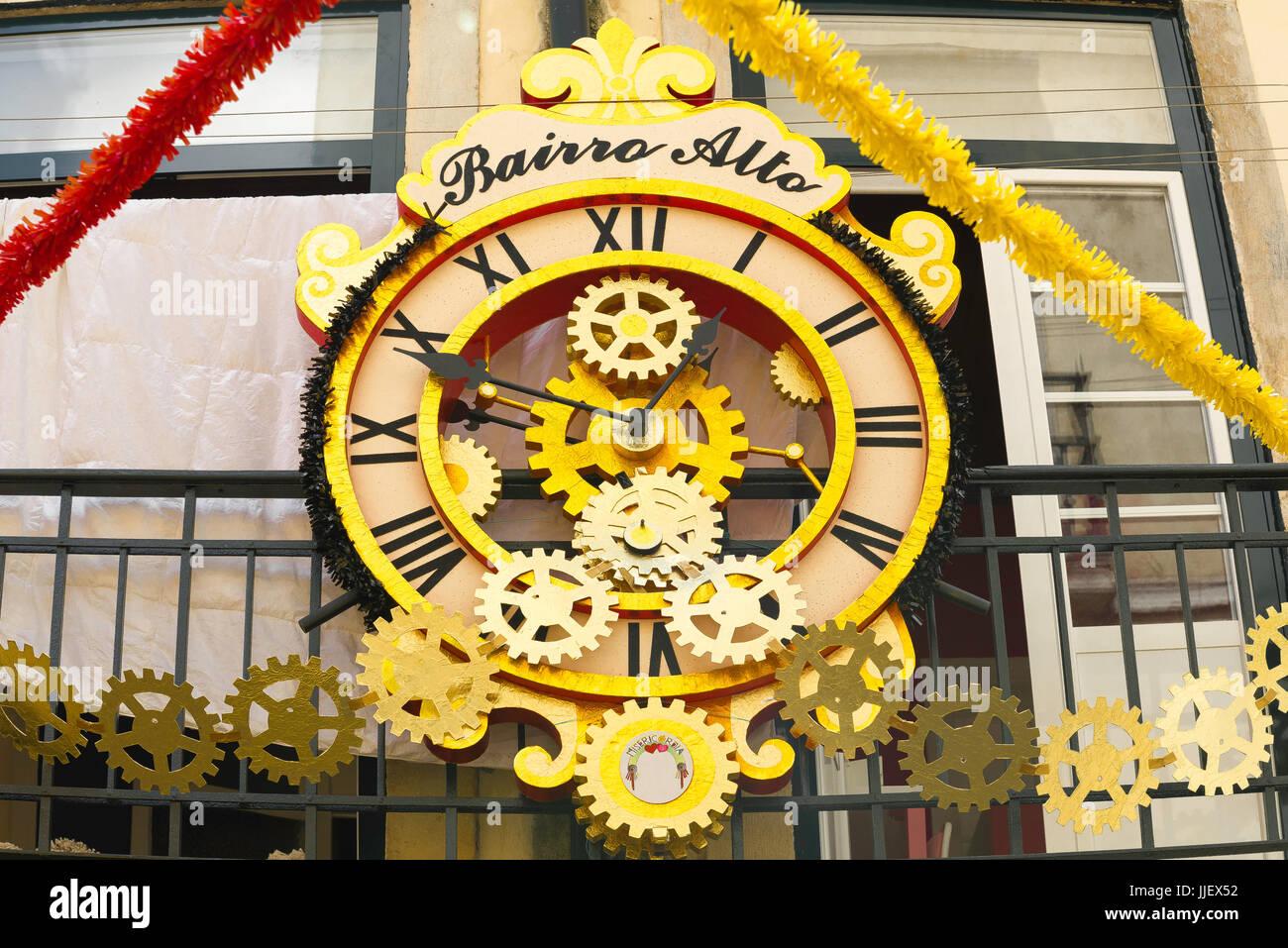 Lisbon Bairro Alto, a huge gold-coloured clock above a bar in a street in the old town Bairro Alto quarter of Lisbon, - Stock Image