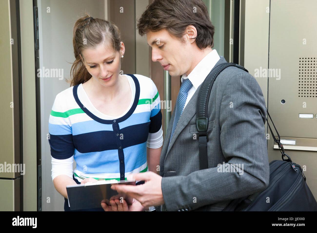 Woman with salesman on the doorstep - Stock Image