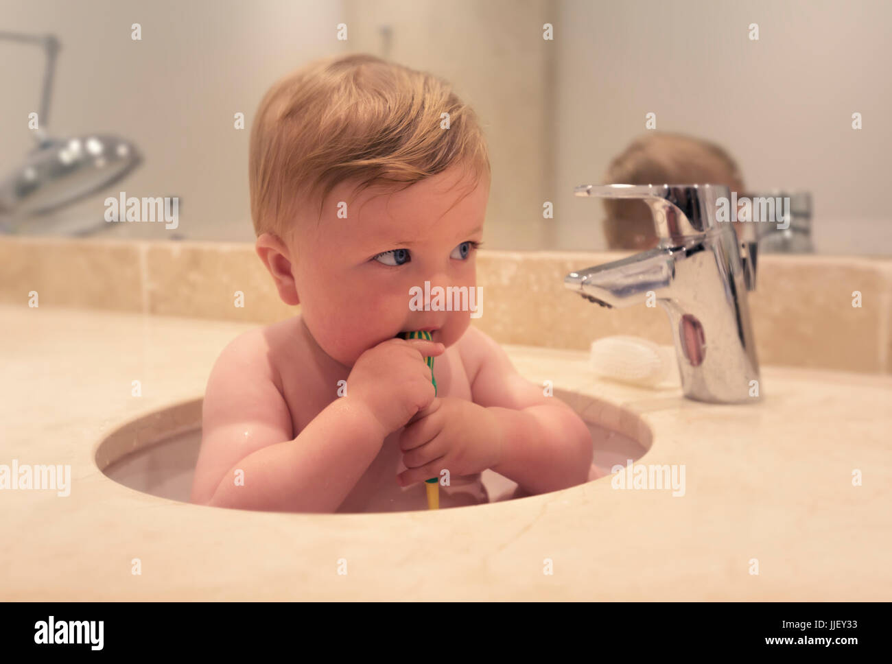 Baby boy sitting in a sink brushing his teeth Stock Photo