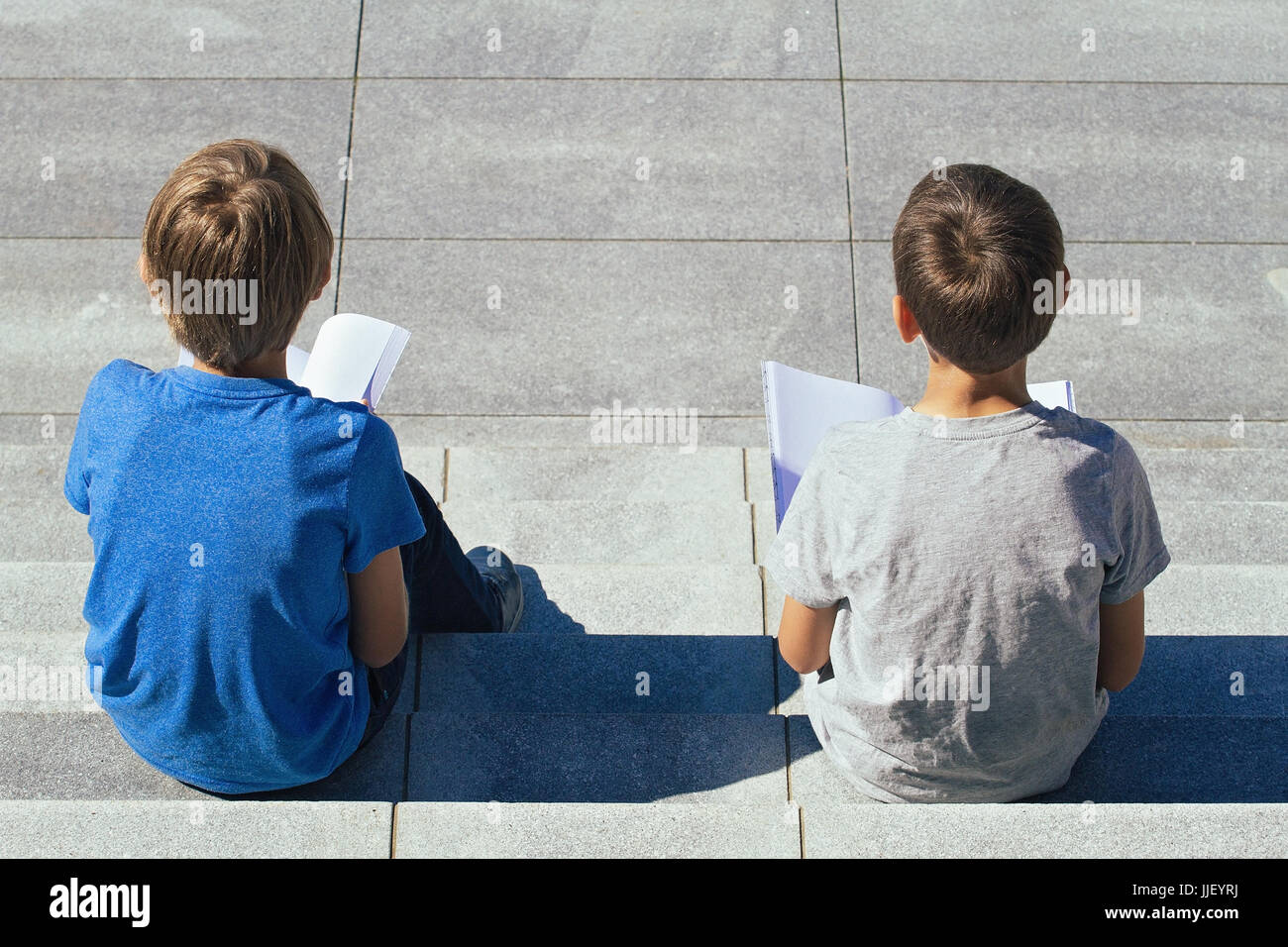Two boys reading books sitting on the stairs outdoors - Stock Image