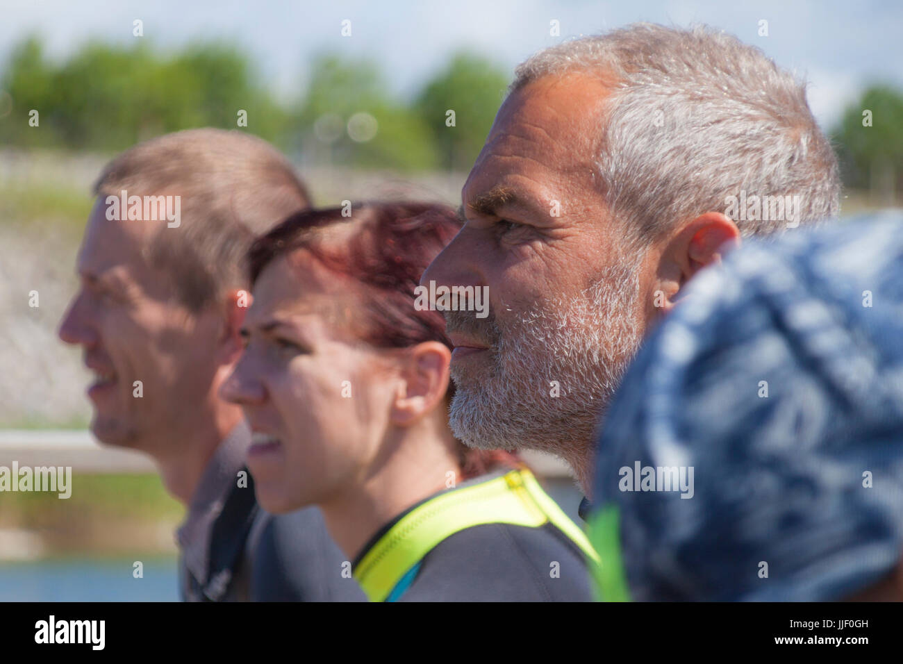 Three people looking into distance - Stock Image