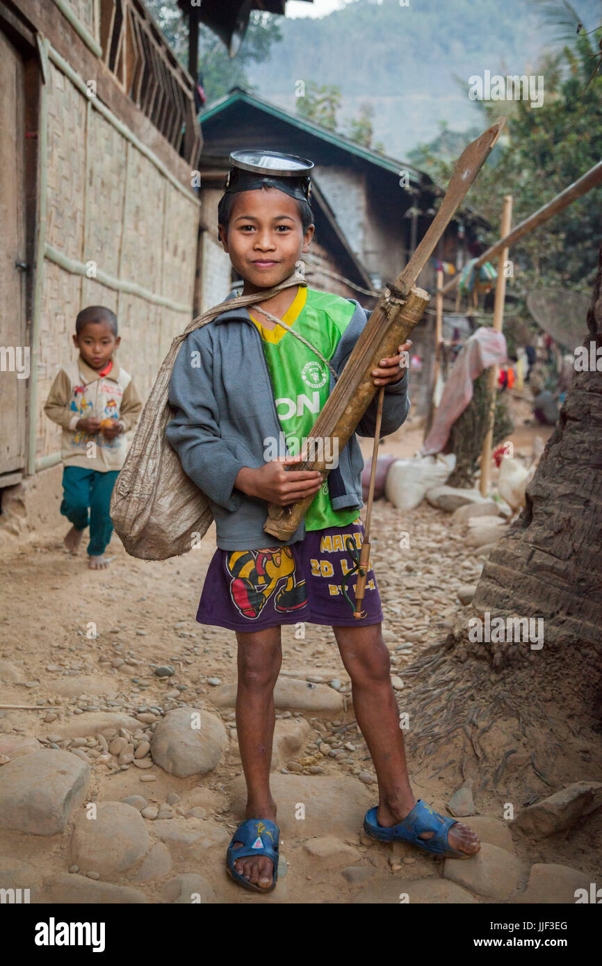 A boy poses proudly with his diving mask, spear gun, and homemade string instrument in Ban Huay Phouk, Laos. - Stock Image
