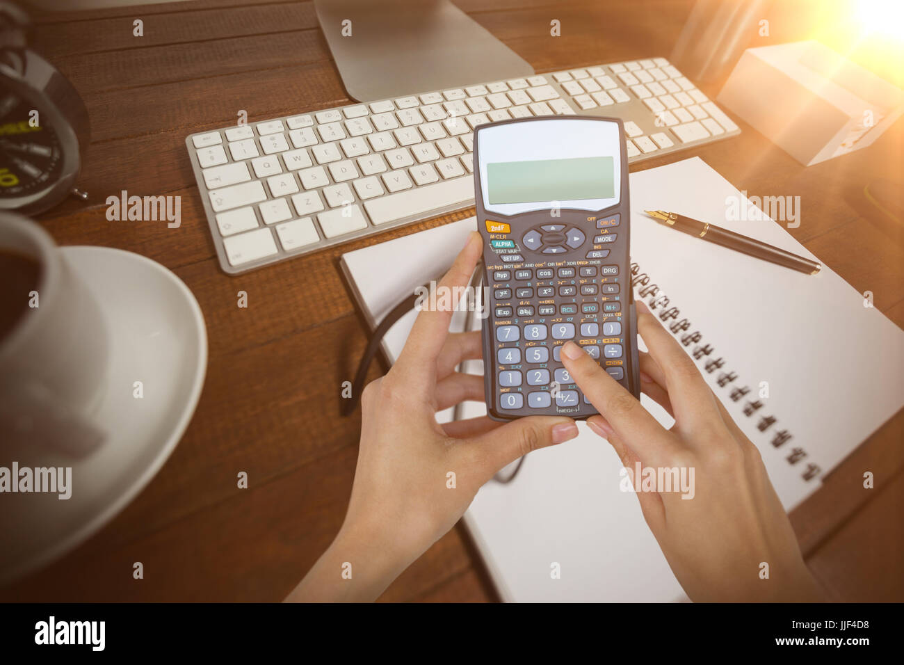 Cropped hands of businesswoman using calculator against notepad with black coffee and spectacle - Stock Image