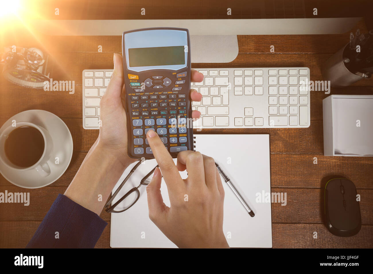 Hands of businesswoman using calculator against overhead view of spiral notepad with black coffee and spectacle - Stock Image