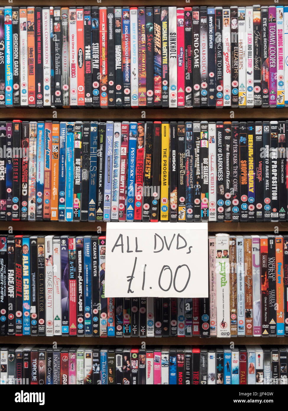 A close up of DVDs for sale on a market stall in the UK - Stock Image