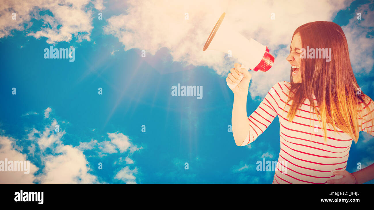 Young woman yelling with megaphone  against view of beautiful sky and clouds - Stock Image