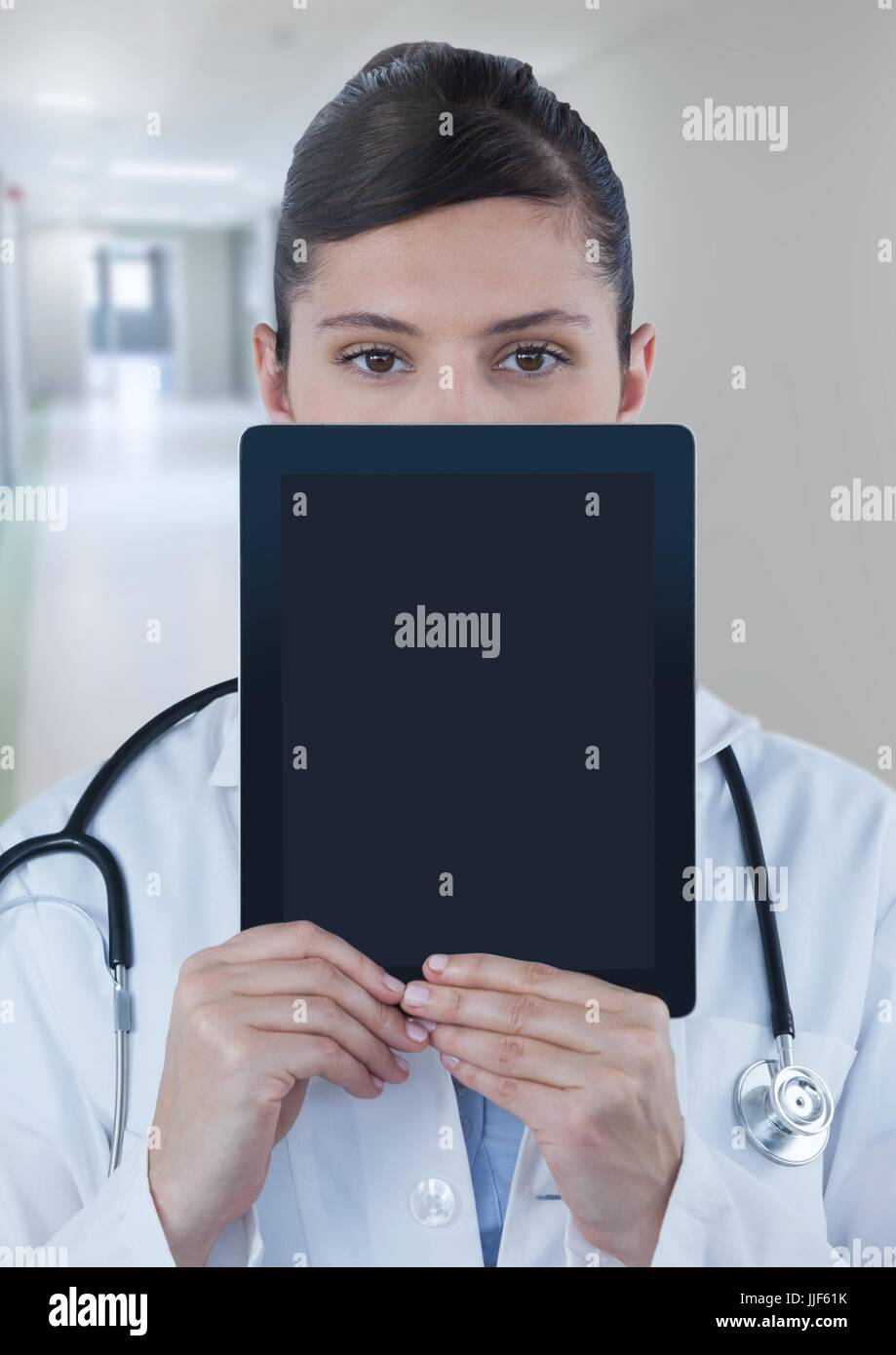 Digital composite of Doctor holding tablet over face in corridor - Stock Image